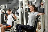 Young Athletic Woman Exercising In Gym. Man And Woman Training At Fitness Center. Attractive Female  poster