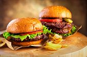 Hamburger and Double Cheeseburger with fries rotated on wooden table background. Cheeseburgers on fr poster