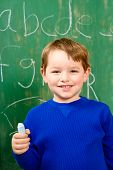 Young boy in front of chalk board
