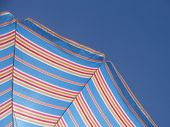 Colourful beach umbrella over a blue sky