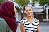 Cheerful african american woman in conversation with muslim girl. Happy multiethnic friends in stree poster