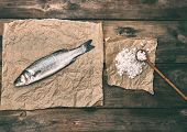 Fresh Whole Sea Bass Fish On Brown Crumpled Paper And Salt With A Wooden Spoon, Top View, Copy Space poster