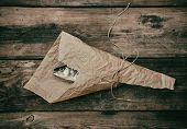 Fresh Whole Sea Bass Fish Wrapped In A Brown Paper  And Tied With A Rope, Wooden Table, Top View poster