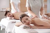 Romantic Young Couple Enjoying Back Massage In Spa Salon poster