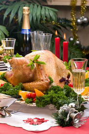 foto of christmas dinner  - Garnished roasted turkey on Christmas decorated table with candles and flutes of champagne - JPG