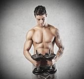 Muscular young man holding two dumbbells
