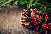 Pine cone and spruce twigs on wooden background
