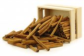 dried cinnamon sticks in a wooden box on a white background