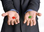 Businessman hands holding two pills.