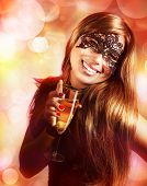 Photo of sexy young lady wearing black lace mask isolated on blur background, luxury woman holding glass of champagne in hand, New Year carnival, Christmas masquerade, dance club, mystery night party