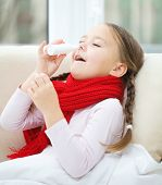 Little girl spraying her nose with nasal spray while sitting on sofa