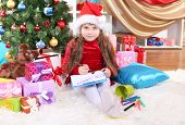 Beautiful little girl in red dress writes letter to Santa Claus in festively decorated room