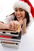 Cheerful Student Wearing Christmas Hat With Stack Of Books