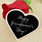 sentence happy grandparents day written with chalk on a heart-shaped blackboard with a red rose in t