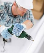 interior design and home renovation concept - man in helmet with electric drill making hole in wall