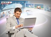 business, technology, internet and news concept - businessman with laptop pc and virtual screens reading news