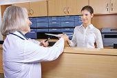 Senior doctor at hospital reception getting medical records