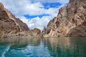 Fine Kelsu mountain lake with grandiose rocks and the dark blue sky with clouds