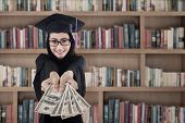 Female Graduate Holding Money At Library