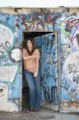 Shirtless woman in jeans standing at the entrance by graffiti wall and door