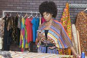 Attractive African American female fashion designer using cell phone