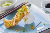 stock photo of masago  - Fried breaded ahi tuna resting on a ball of rice drizzled with masago mayonnaise and sprinkled with green onions and masago also known as capelin fish roe