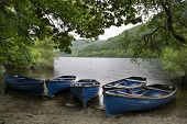 Old Fashioned Retro Style Rowing Boats On Shore Of Lake In Summer
