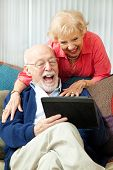 Senior couple having fun and laughing while using their tablet pc computer.