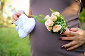 Pregnant Woman Holding Bouquet Of Rose And Booties