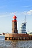 red lighthouse at the harbor entrance of Bremerhaven, contemporary buildings in background
