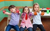 Portrait of playful little girl with friends showing colored palms in art class