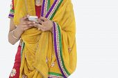 stock photo of dupatta  - Midsection of woman in Indian clothing using cell phone over white background - JPG
