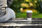 Man with coffee on a bench in the park