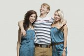 Portrait of two young women in similar jumpsuits standing with happy male friend over gray backgroun
