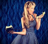 Charming pin-up woman with retro hairstyle and make-up talking on the phone.