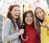 stock photo of 15 year old  - Three Teenage Girl Sheltering From Rain Beneath Umbrella - JPG