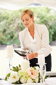 stock photo of marquee  - Wedding Planner Checking Table Decorations In Marquee - JPG
