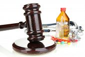 Medicine law concept. Gavel and pills isolated on white