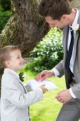 Page Boy Handing Wedding Ring To Groom