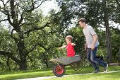 Father Giving Son Ride In Wheelbarrow