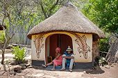 Sotho Couple Wearing Tribal Handmade Dress Sitting Near Traditional Native House.