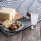 foto of ouzo  - Delicious Cheese and olives on table close up - JPG