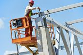 worker joiner in uniform and safety protective equipment at metal construction frames installation a