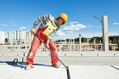 builder worker with metal crow bar installing concrete floor slab panel at building construction sit