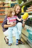 Mother woman and little girl choosing melon during family shopping at fruit vegetable supermarket st