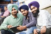 stock photo of sikh  - Group portrait of smiling authentic native indian punjabi sikh men in turban with bushy beard - JPG