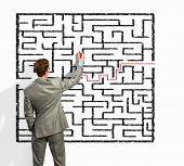stock photo of maze  - Back view image of young businessman trying to find way out of maze - JPG