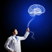 Image of young doctor neurologist against dark background