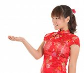 Pretty Asian female with Chinese traditional dress cheongsam or qipao hand showing blank space. Chin
