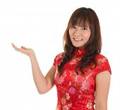 Pretty Asian woman with Chinese traditional dress cheongsam or qipao hand showing blank space. Chine